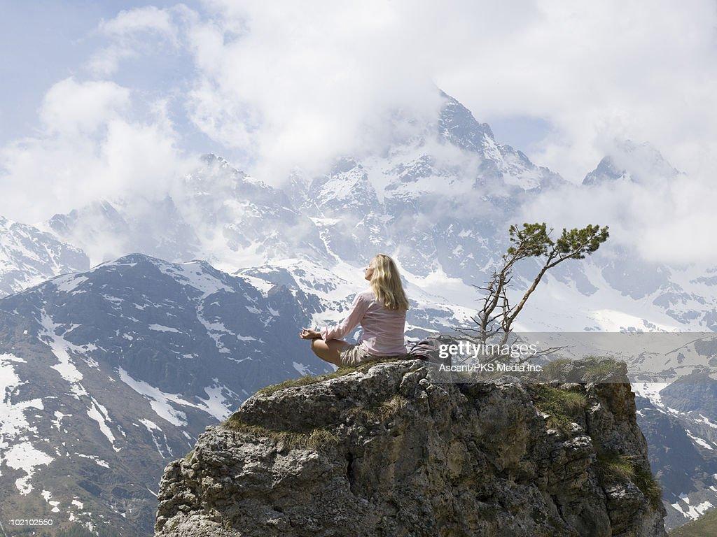 Woman practices yoga on summit of pinnacle, tree : Stock Photo