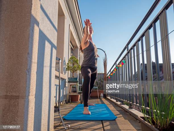 a woman practices yoga on the balcony of her apartment - praticare foto e immagini stock