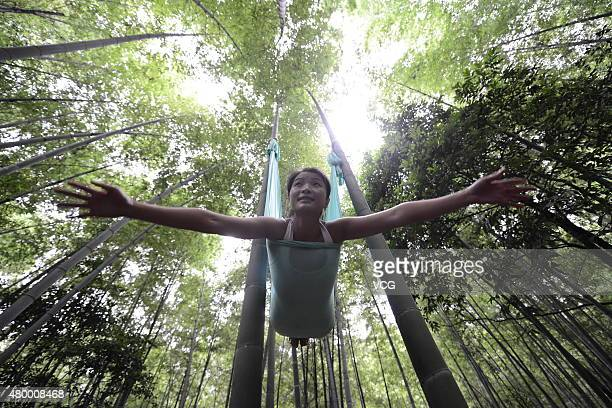A woman practices yoga with hammock and hang in the air in the bamboo forest on July 4 2015 in Changsha China