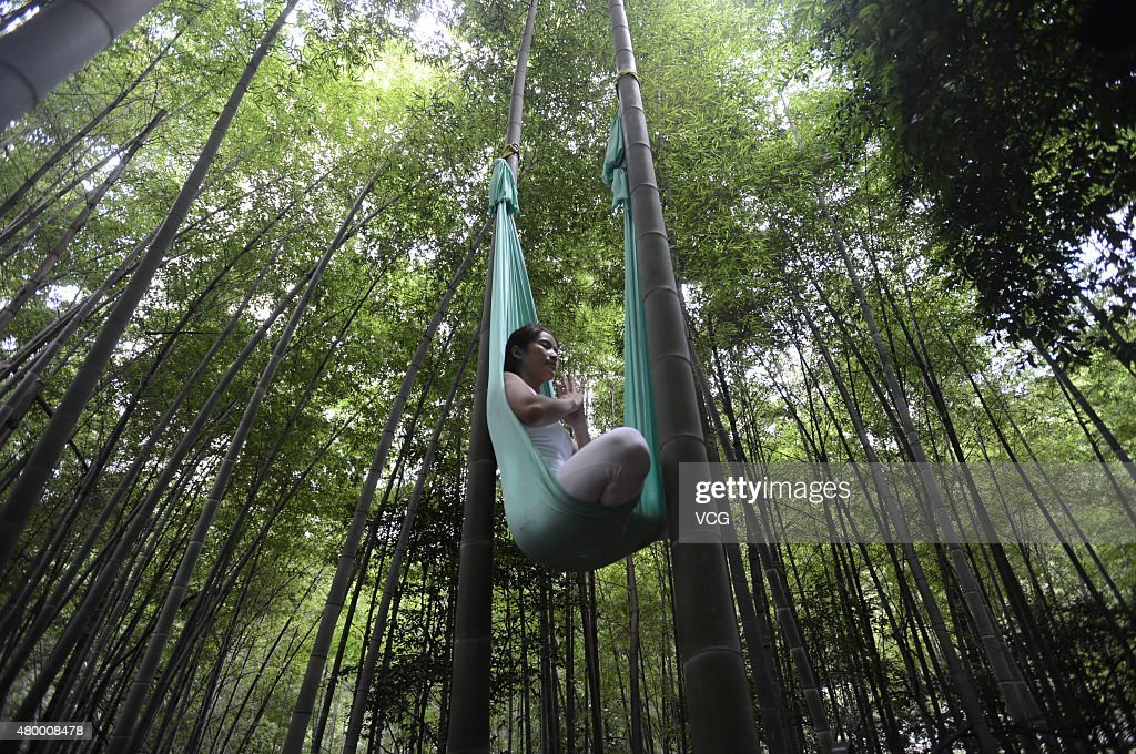 A woman practices yoga with hammock and hang in the air in the bamboo forest on July 4, 2015 in Changsha, China.