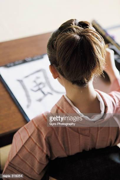 woman practicing a shodo - 書道 ストックフォトと画像