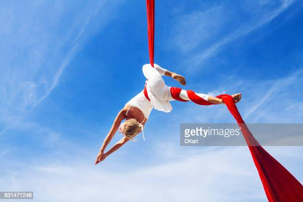 woman practicing aerial silk yoga outdoors - silk stock pictures, royalty-free photos & images