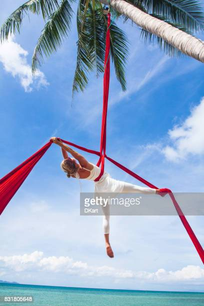 woman practicing aerial silk yoga outdoors - acrobatic activity stock photos and pictures