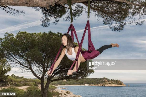 Woman practicing aerial yoga outdoors