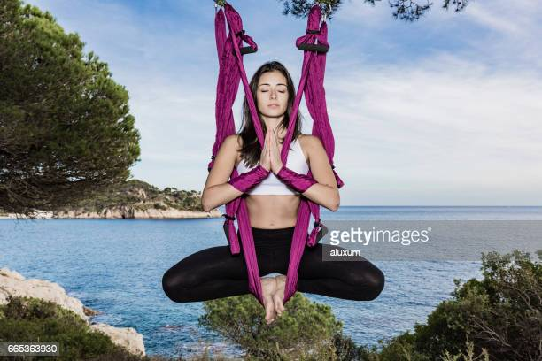 woman practicing aerial yoga outdoors - yogi stock photos and pictures