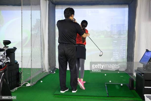 a woman practicing at a golf studio and a man with a coach. - sport set competition round stock pictures, royalty-free photos & images