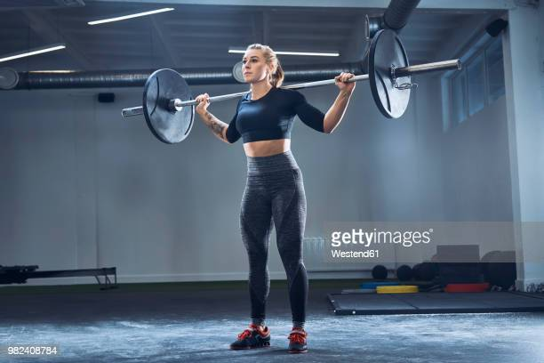 woman practicing barbell squat at gym - picking up stock pictures, royalty-free photos & images