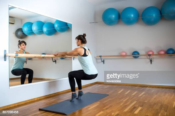 woman practicing barre pilates - barre stock photos and pictures