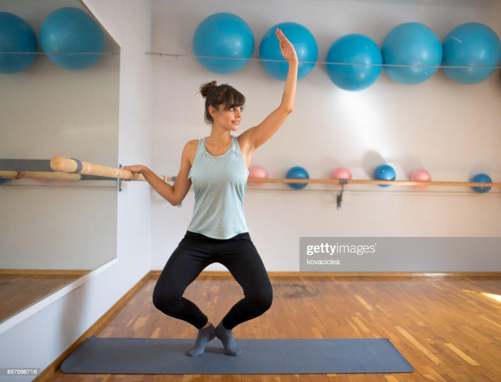Woman practicing barre pilates : Stock Photo