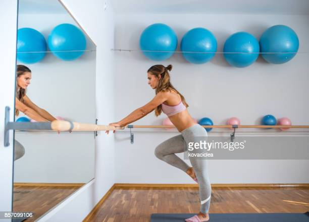 Woman practicing barre pilates