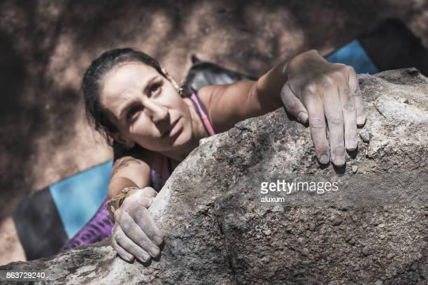 Woman practicing boulder rock climbing