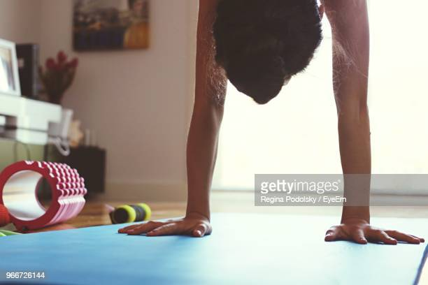 woman practicing handstand on exercise mat - handstand stock pictures, royalty-free photos & images