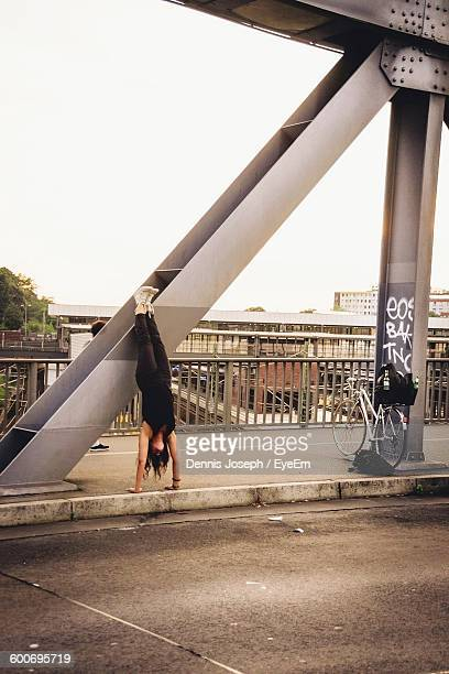 Woman Practicing Headstand On Sidewalk