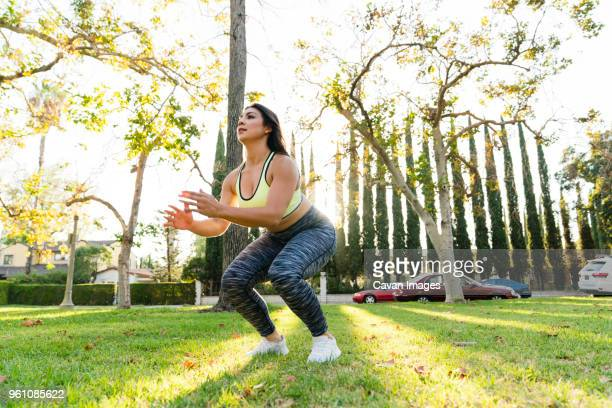 woman practicing jump squats in park - crouching stock pictures, royalty-free photos & images