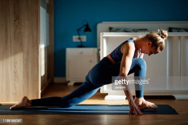 woman practicing lizard pose - active lifestyle stock pictures, royalty-free photos & images