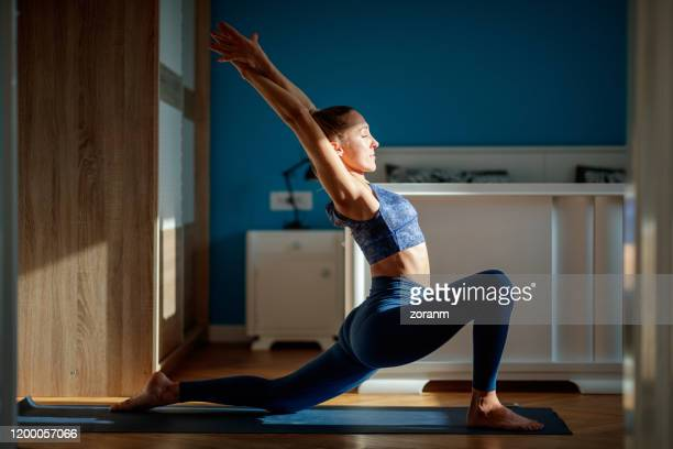 woman practicing low lunge pose - low stock pictures, royalty-free photos & images