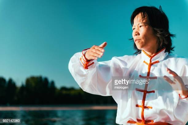 Woman Practicing Martial Arts At Lake Against Sky