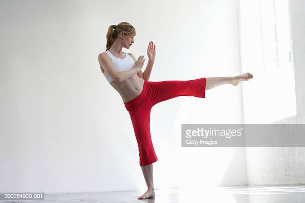 woman practicing martial arts kick - pedal pushers stock pictures, royalty-free photos & images