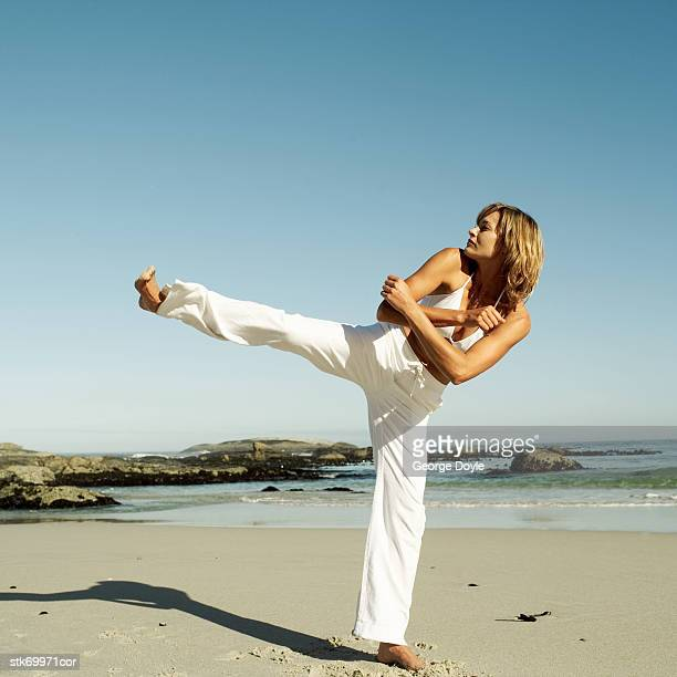 woman practicing martial arts on the beach