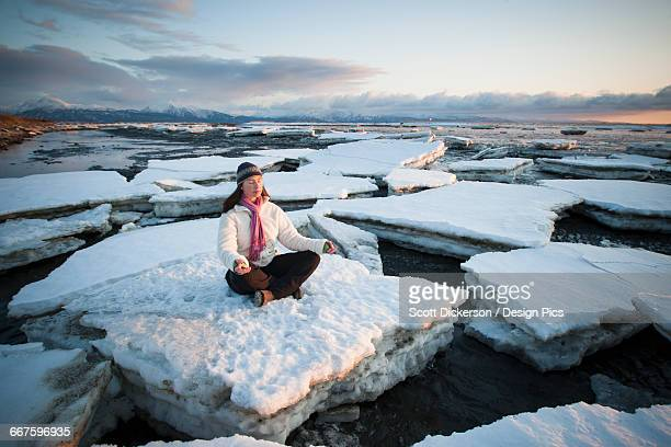 Woman practicing meditation on ice chunks stacked against the Homer Spit, Southcentral Alaska