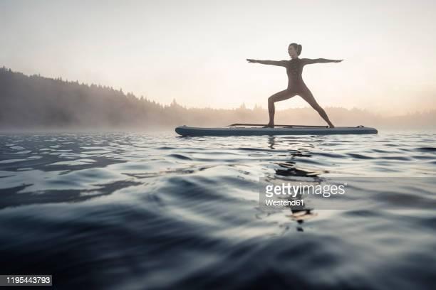 woman practicing paddle board yoga on lake kirchsee in the morning, bad toelz, bavaria, germany - gleichgewicht stock-fotos und bilder