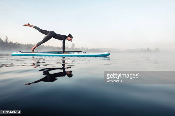 woman practicing paddle board yoga on lake kirchsee in the morning, bad toelz, bavaria, germany - image technique stock pictures, royalty-free photos & images