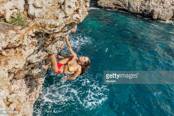 woman practicing psicobloc rock climbing in minorca spain - arrampicata su roccia foto e immagini stock