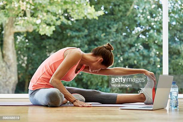 Woman practicing stretching exercise at gym