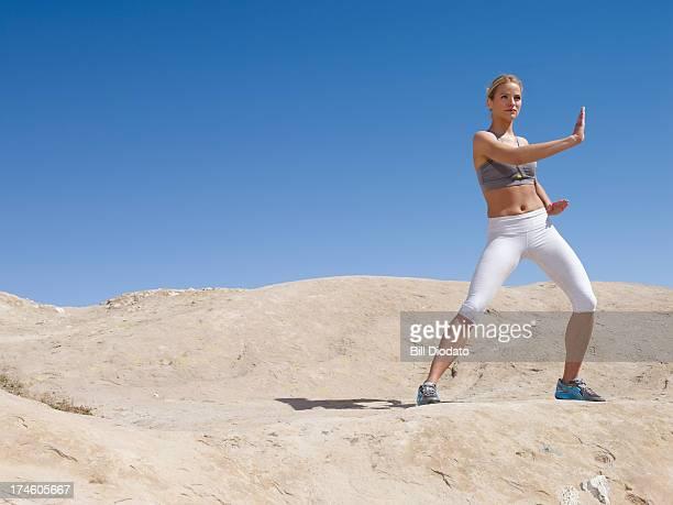 Woman practicing tai chi on desert rocks