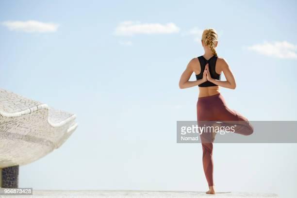 Woman practicing tree pose yoga on terrace