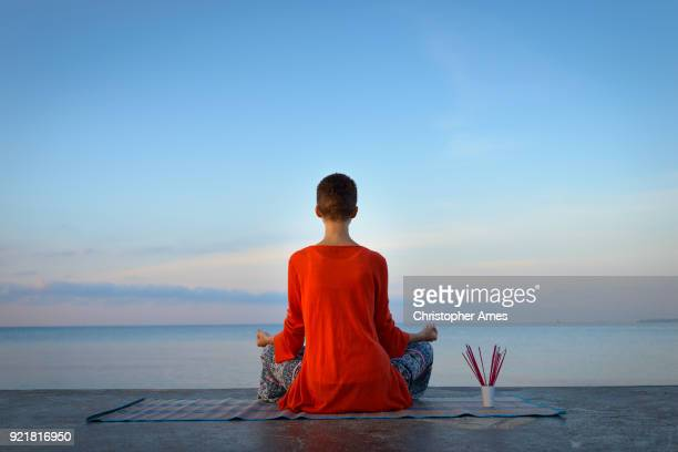 woman practicing yoga and meditation at dawn - incense stock photos and pictures