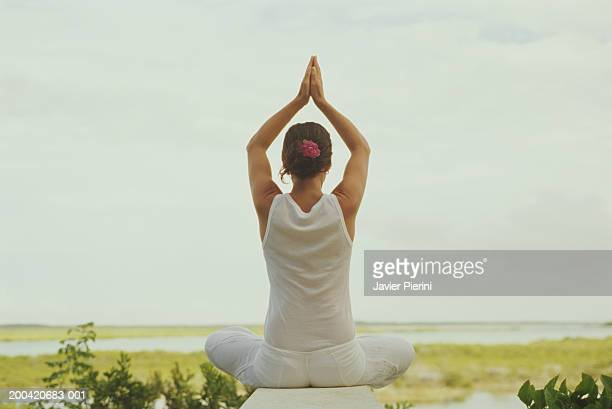 Woman practicing yoga, arms raised, rear view