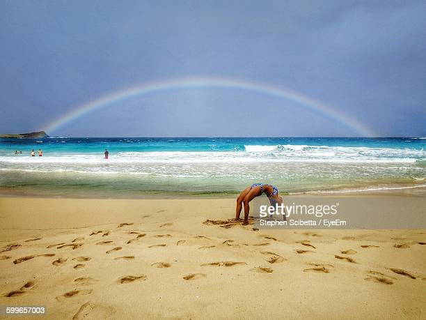 Woman Practicing Yoga At Beach Against Cloudy Sky