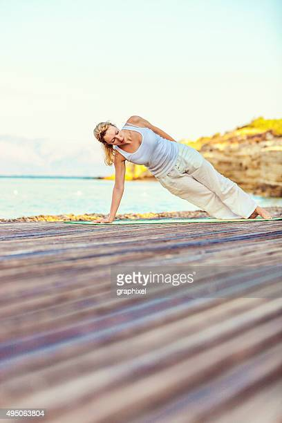 woman practicing yoga at beach - graphixel stock pictures, royalty-free photos & images