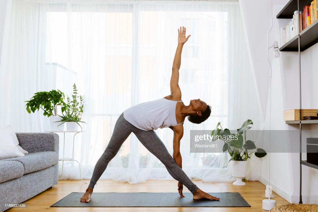 Woman practicing yoga at home : Foto de stock