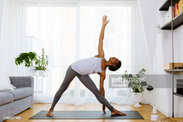 woman practicing yoga at home - yoga stockfoto's en -beelden