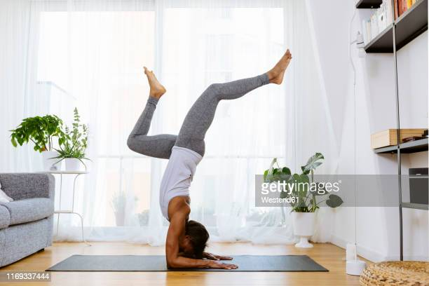 woman practicing yoga at home - handstand stock pictures, royalty-free photos & images