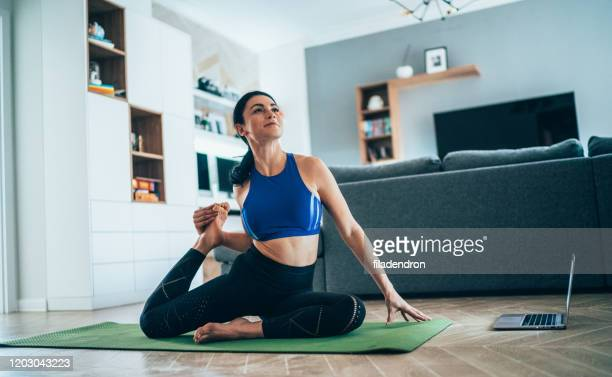 woman practicing yoga at home - pilates stock pictures, royalty-free photos & images