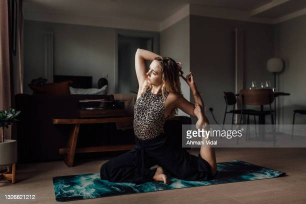 woman practicing yoga at home - one mid adult woman only stock pictures, royalty-free photos & images