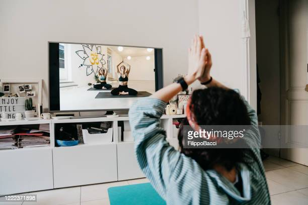 woman practicing yoga at home with a video lesson on the tv - net sports equipment stock pictures, royalty-free photos & images
