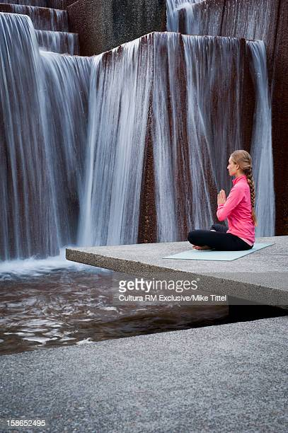 Woman practicing yoga at public fountain