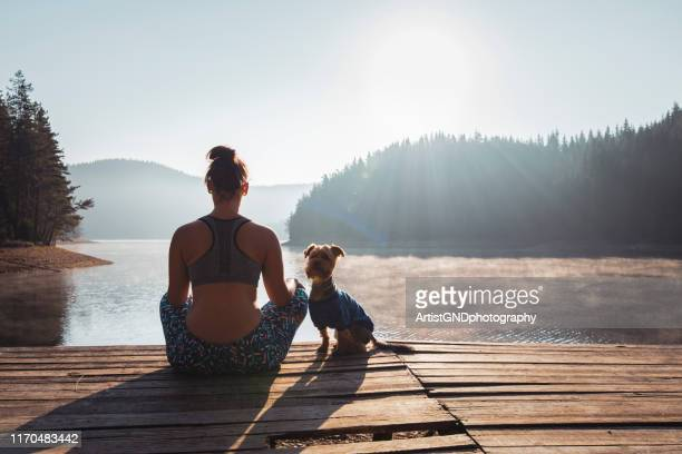 woman practicing yoga at wild lake. - zen foto e immagini stock
