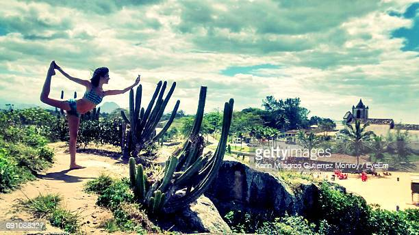 Woman Practicing Yoga By Cactus Plants Against Cloudy Sky