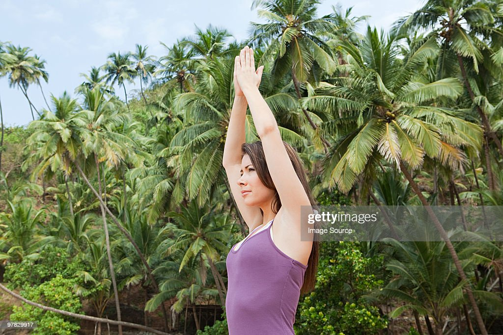Woman practicing yoga by palm trees : Stock Photo