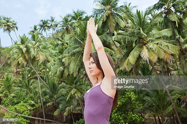Woman practicing yoga by palm trees