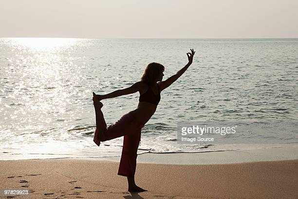 Woman practicing yoga by sea ay sunset
