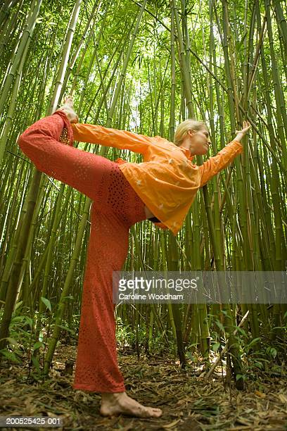 Woman practicing yoga in bamboo forest, side view, (wide angle)