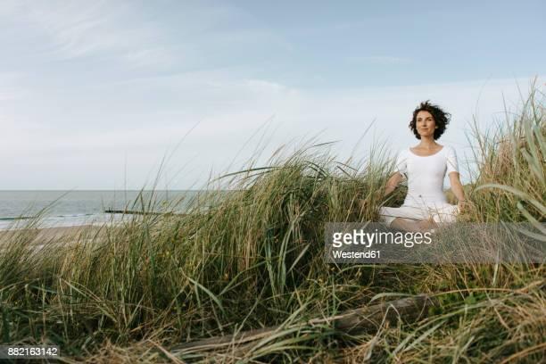 Woman practicing yoga in beach dune