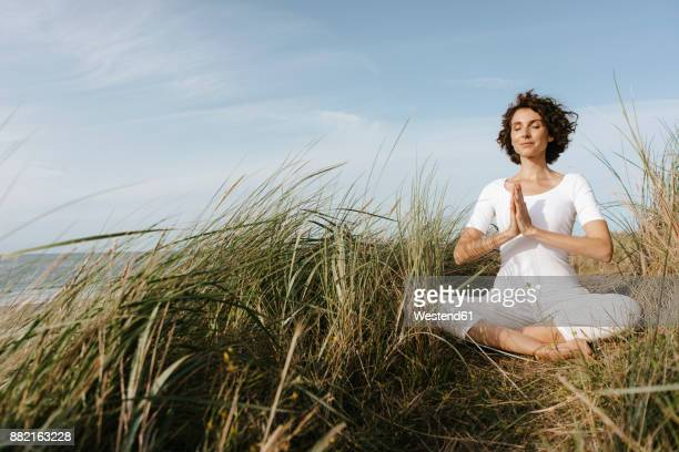 woman practicing yoga in beach dune - meditieren stock-fotos und bilder