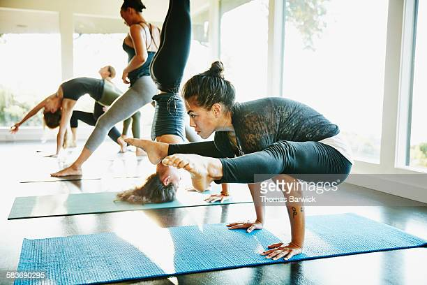 woman practicing yoga in crow pose during class - control stock pictures, royalty-free photos & images